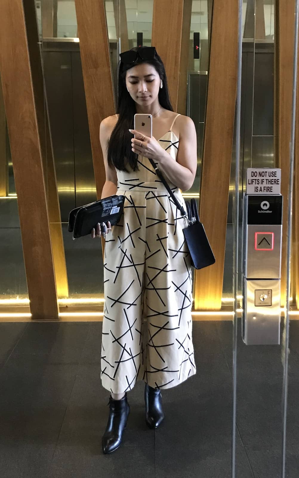 A woman with long dark hair wearing a beige sleeveless wide-leg jumpsuit, taking a selfie in a mirrored surface