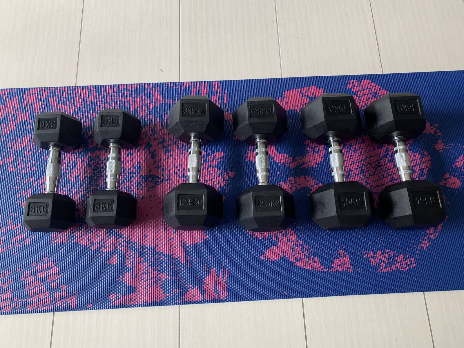 A dark blue yoga mat with a pink pattern. On the mat are three pairs of dumbbells of 8kg, 12.5kg and 15kg.