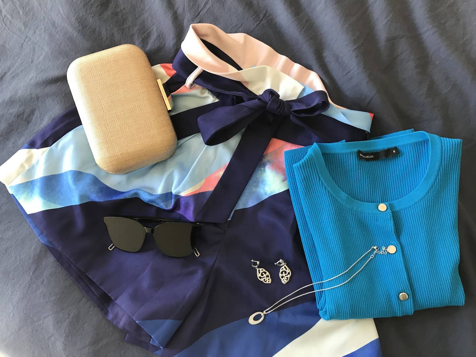 A flatlay of a pair of shorts with white, blue and pink print, with a folded bright blue cardigan, and some jewellery and sunglasses on top.