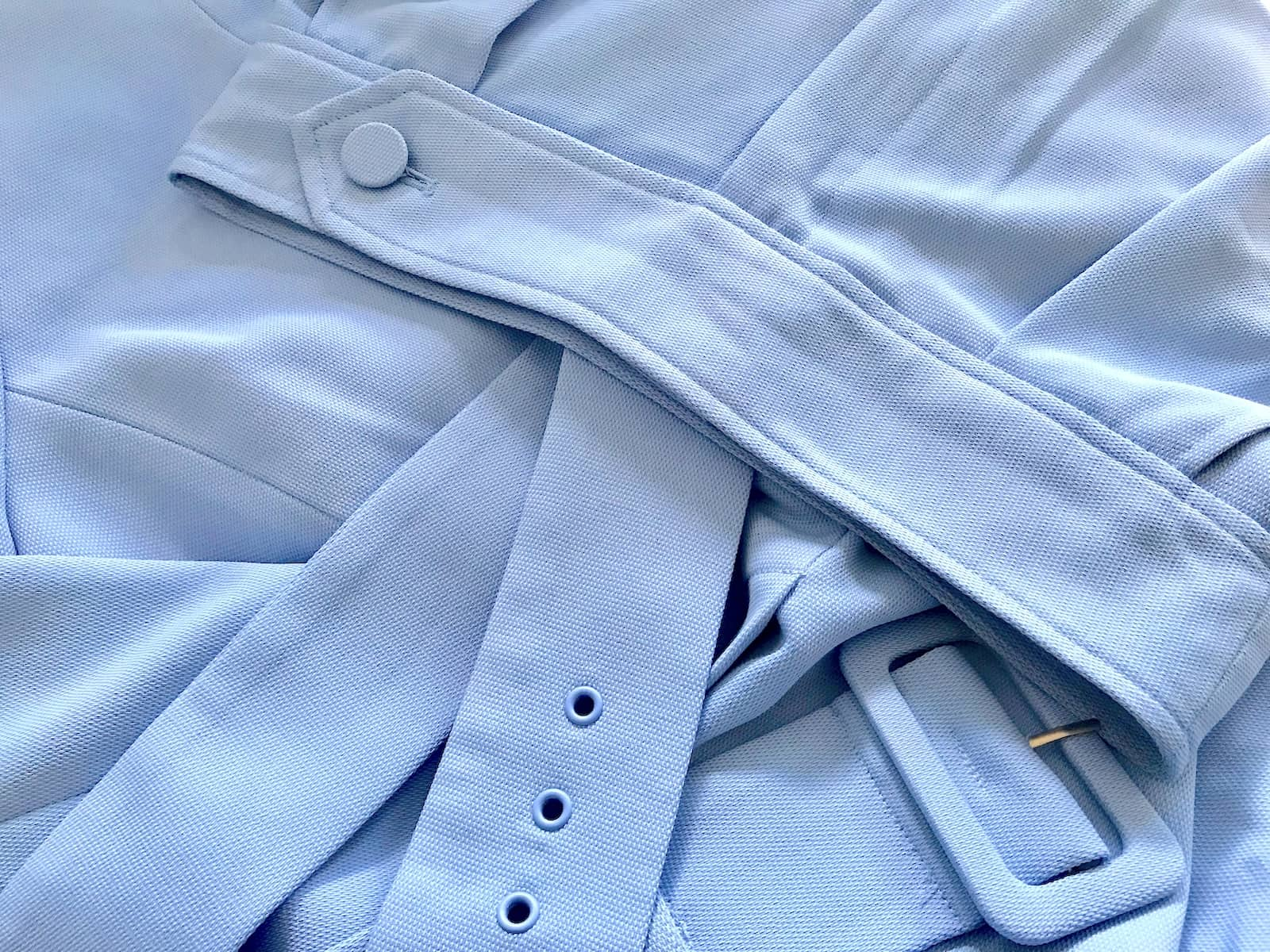 A close-up of the fabric of a pair of pants and blazer, in a cornflower blue colour. The fabric is slightly textured.