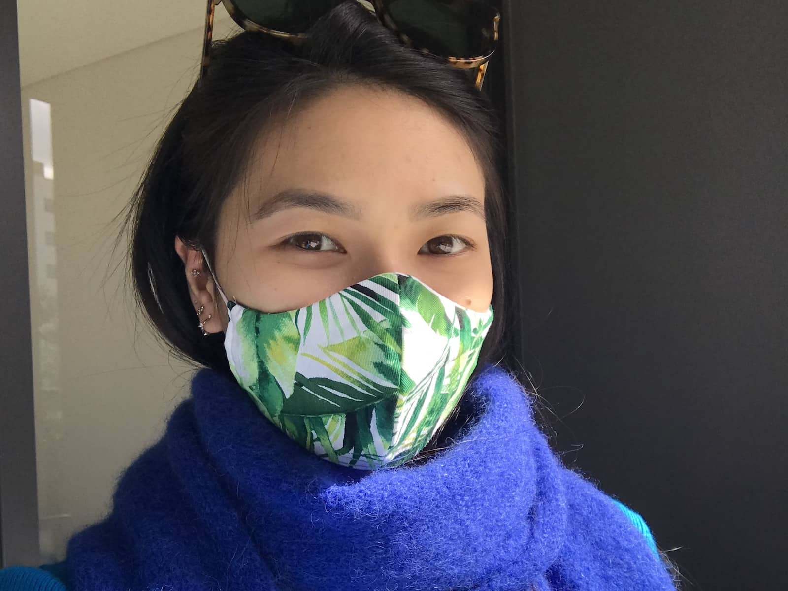 A woman with dark hair wearing a blue scarf and a white mask with green leaves printed on it