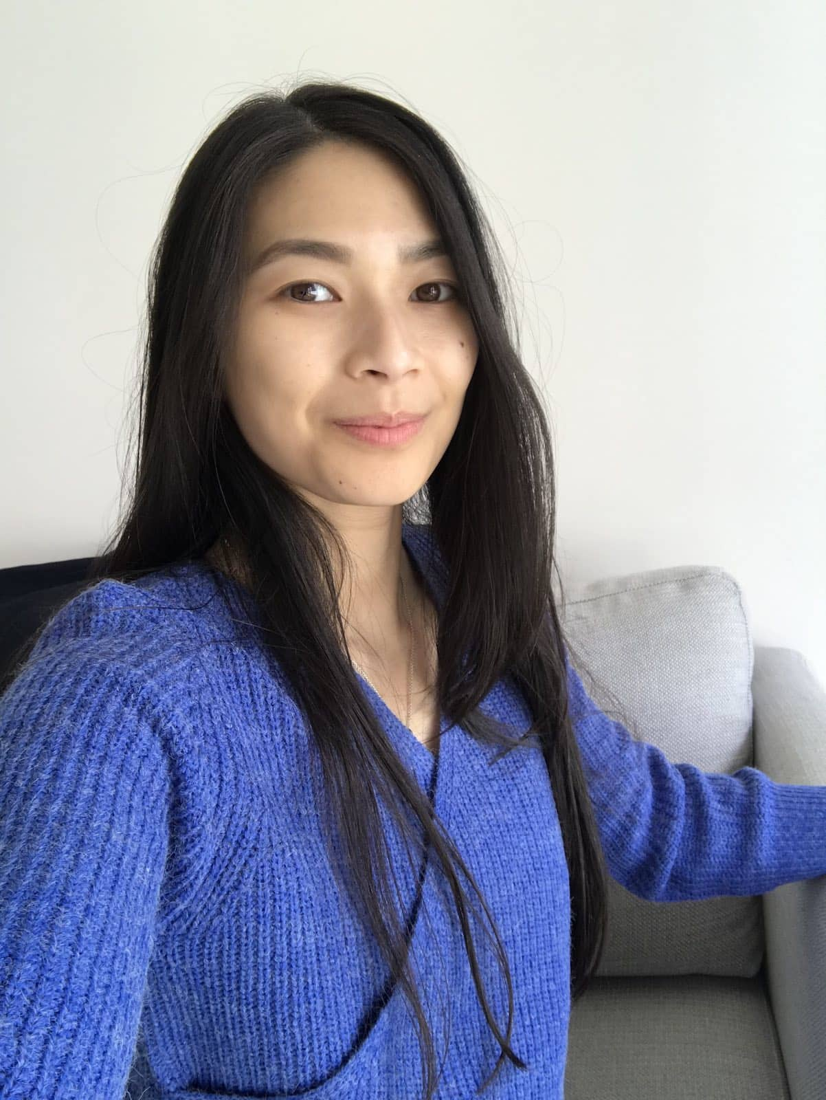 A woman with long dark hair, taking a selfie. She is wearing a blue wrap-front top in a textured knitted fabric