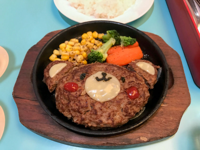 A hamburger steak shaped in an oval with a bear's face created on it with melted cheese, tomato sauce and tiny pieces of seaweed. Two small semicircles of beef patty with melted cheese on top form ears for the bear's face. The meal is served on a hot plate with carrot, corn and broccoli.