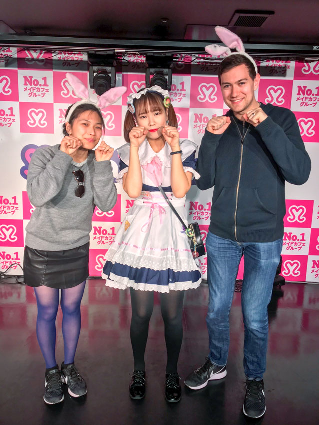 Me, a girl dressed up as a maid, and Nick, with our fists near our face, resembling a cat's paws. Nick and I are wearing headbands with pink and white rabbit ears on top. Hot pink and white wallpaper with hearts and Japanese writing advertise the café.