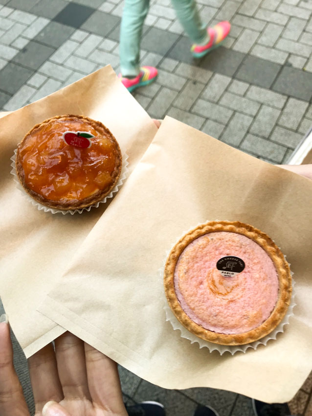 Two round cheese tarts sitting on paper napkins on a person's hand. One tart is glazed like an apple pie and golden brown in colour; the other is pale pink.