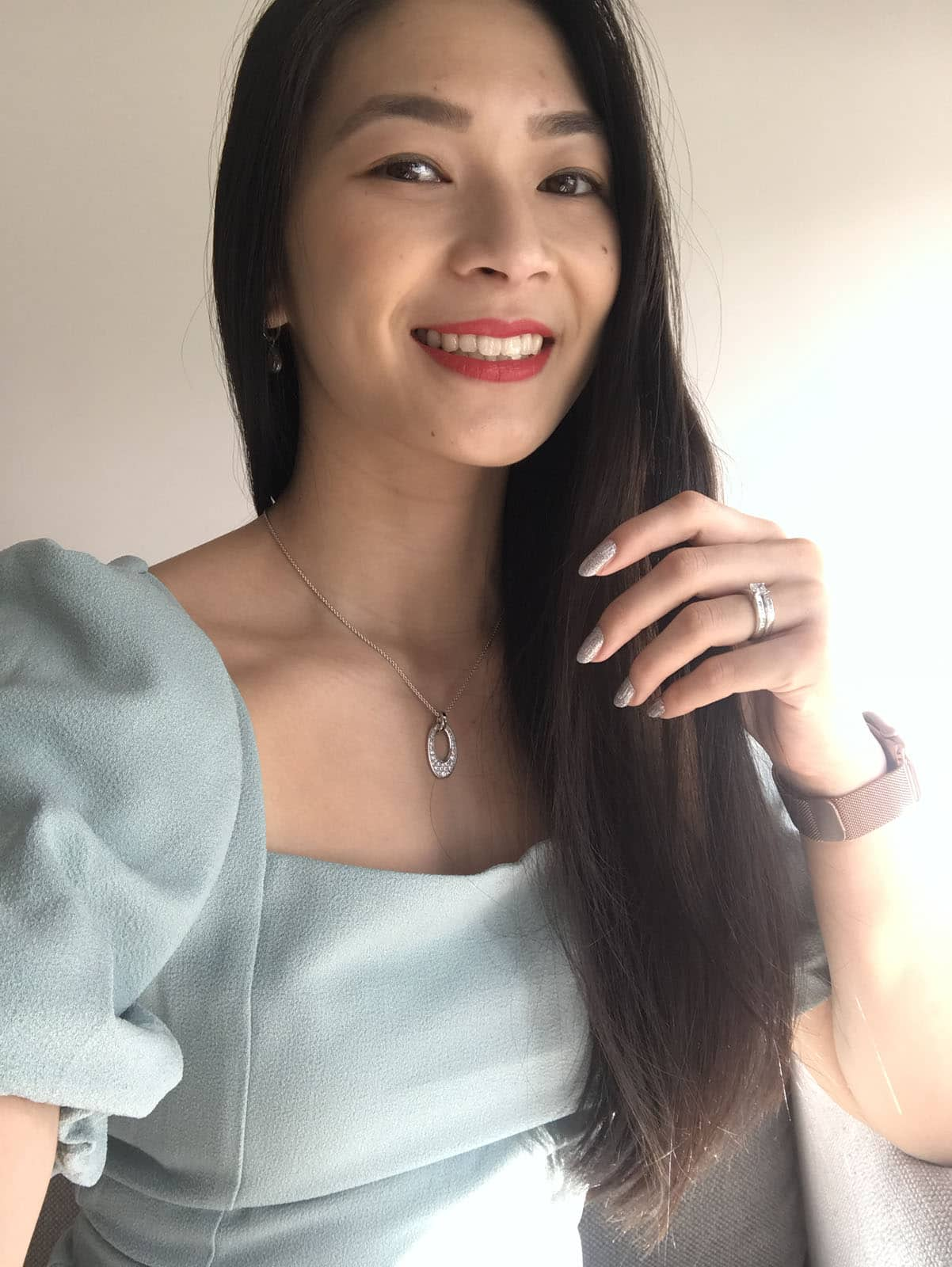 A selfie of a woman with long dark hair, wearing a light seafoam green outfit, with red lipstick on. She is also wearing silver jewellery