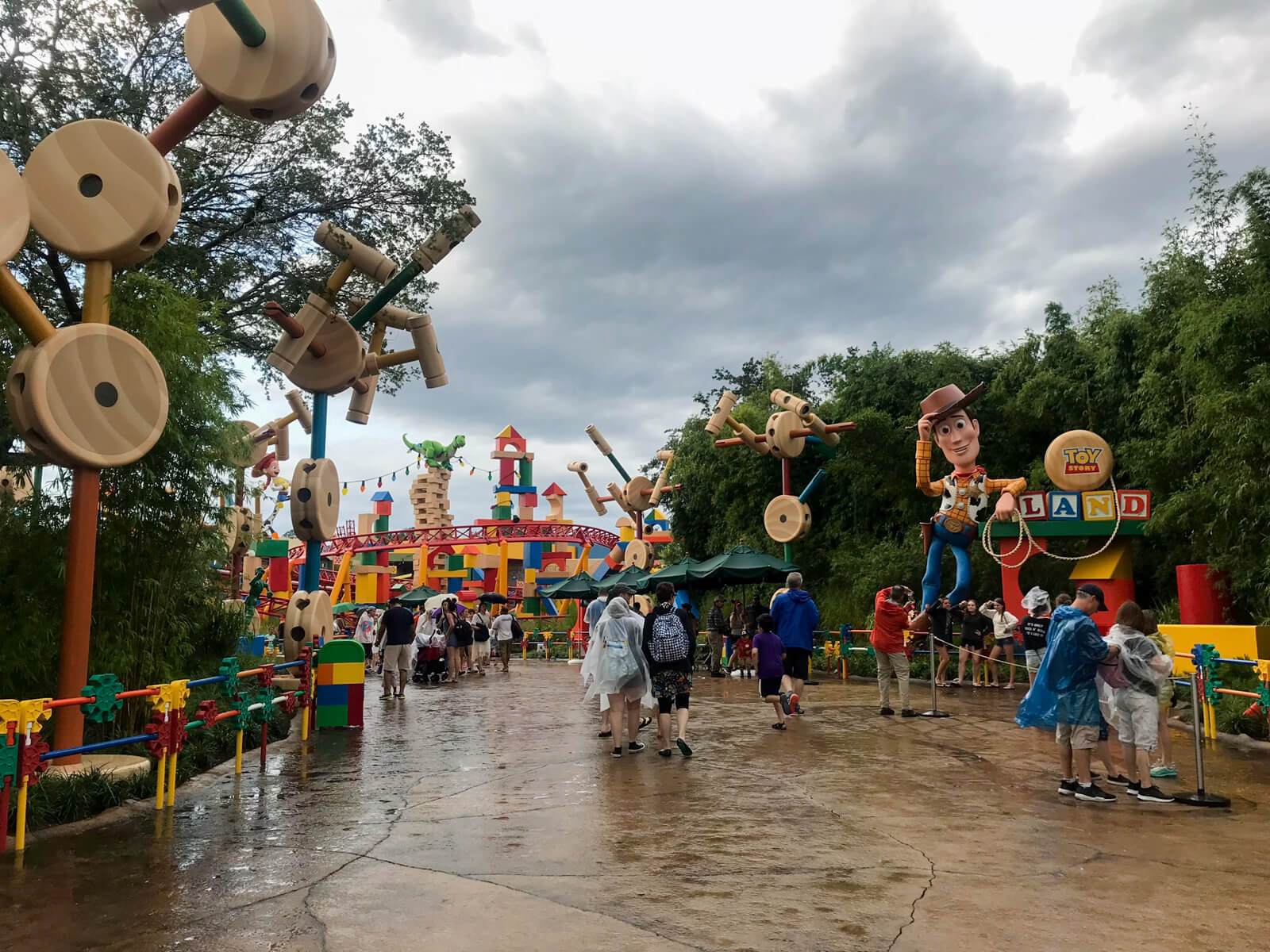 The entrance to an area of a theme park, with statues resembling life-size toys at the edges of the path. All the statues are colourful or resemble wood. The path is very wet and the sky is cloudy.