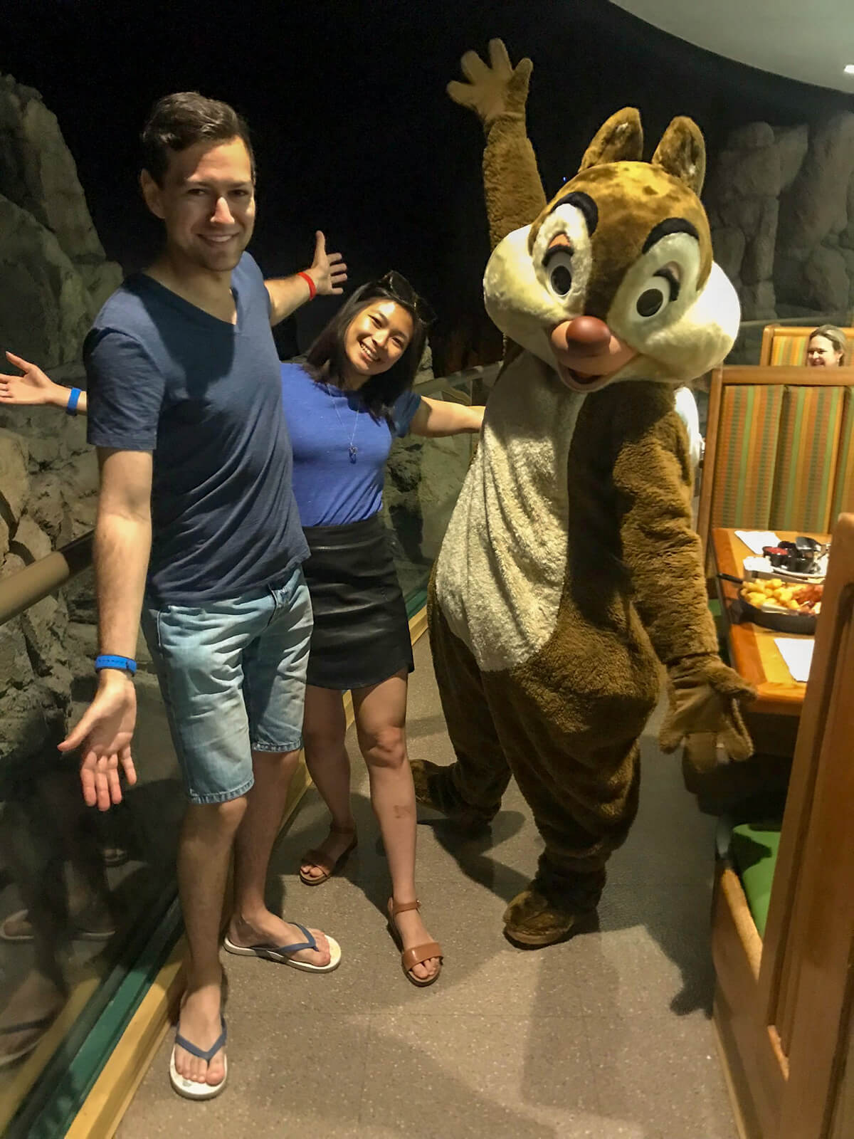A man and woman with their arms outstretched, alongside someone in a chipmunk costume making the same arm movement