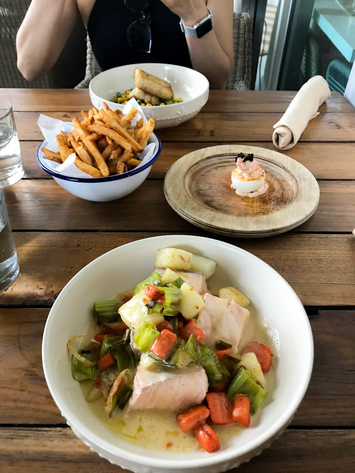 A bowl with cooked fish and vegetables with a soupy base. It's sitting on a wooden table, with a bowl of chips, another dish consisting of an egg decorated with seafood, and a bowl in the distance also containing fish and vegetables