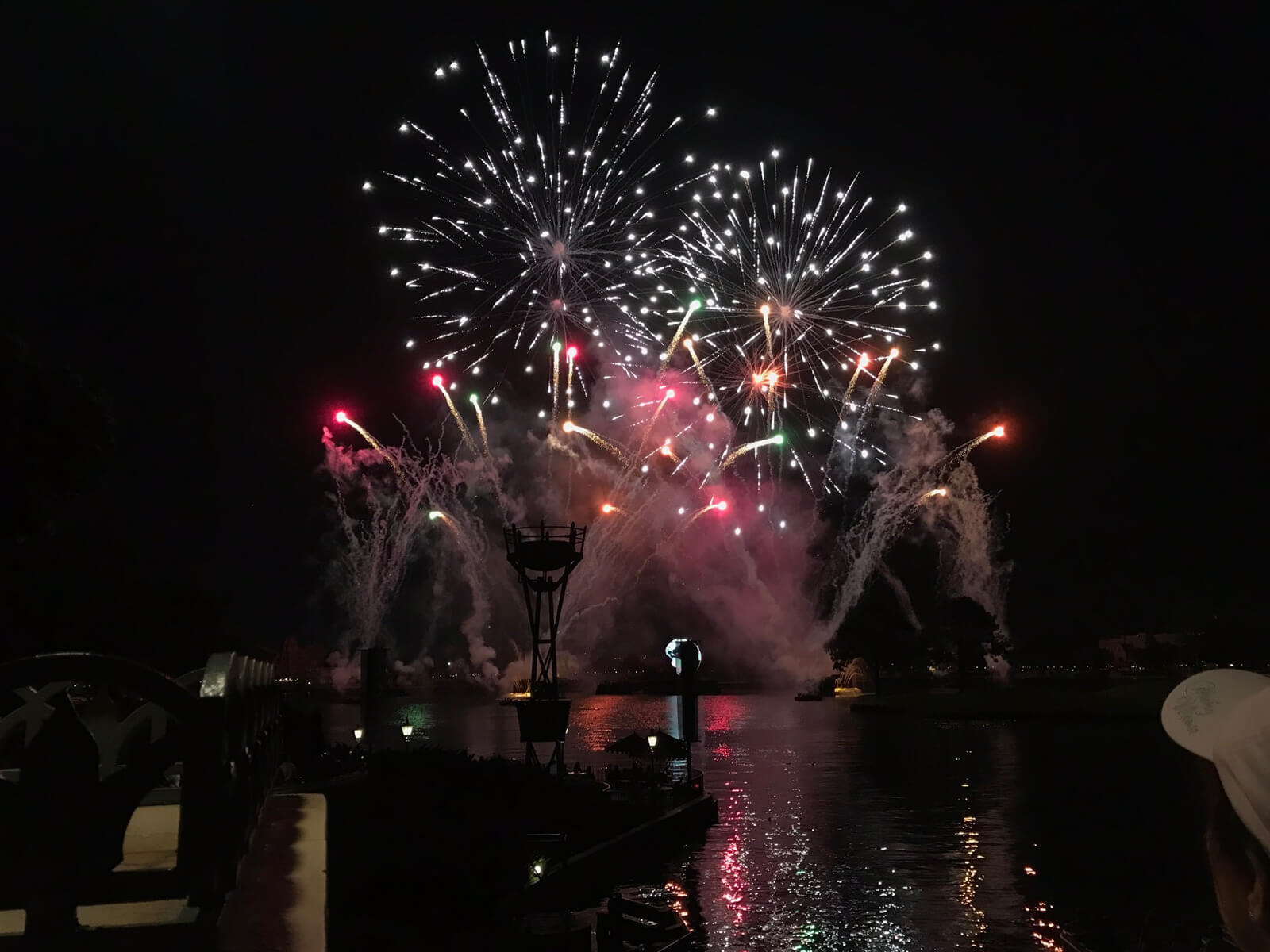 A large display of fireworks and smoke on water on a dark night