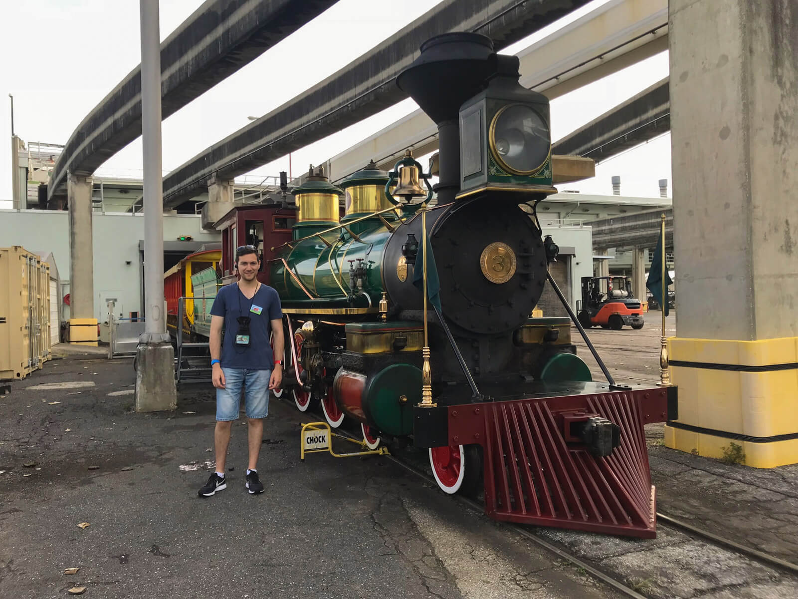 A man with a blue t-shirt and shorts standing next to a green and dark red steam locomotive