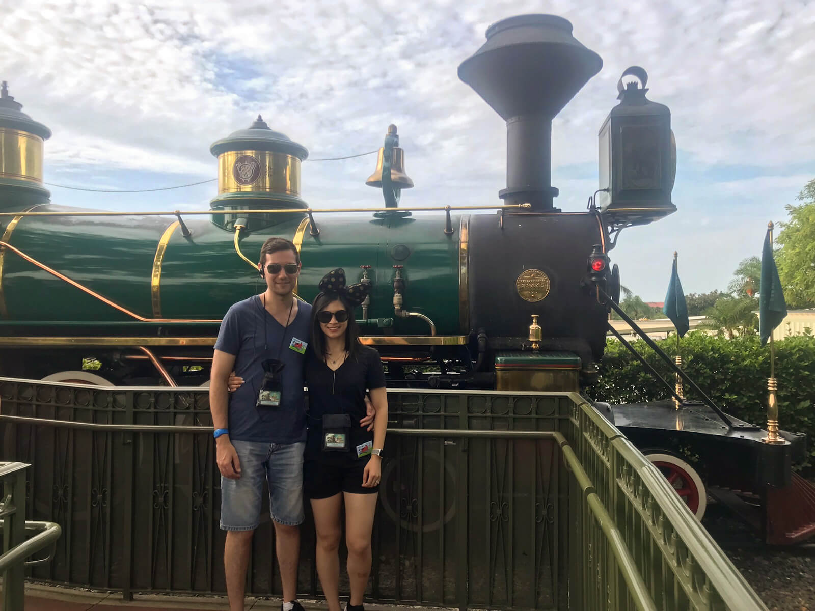 A man and woman standing in front of a green steam train. They are wearing sunglasses and have their arms around each other.