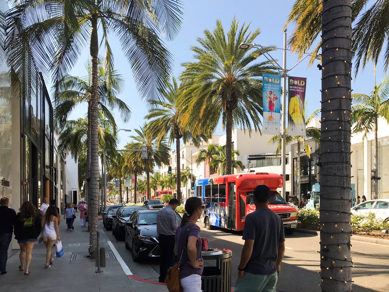 A street with palm trees down the side of the street. The tree trunks have fairy lights wrapped around them. There are cars parked down the side of the street and people walking on the sidewalk.