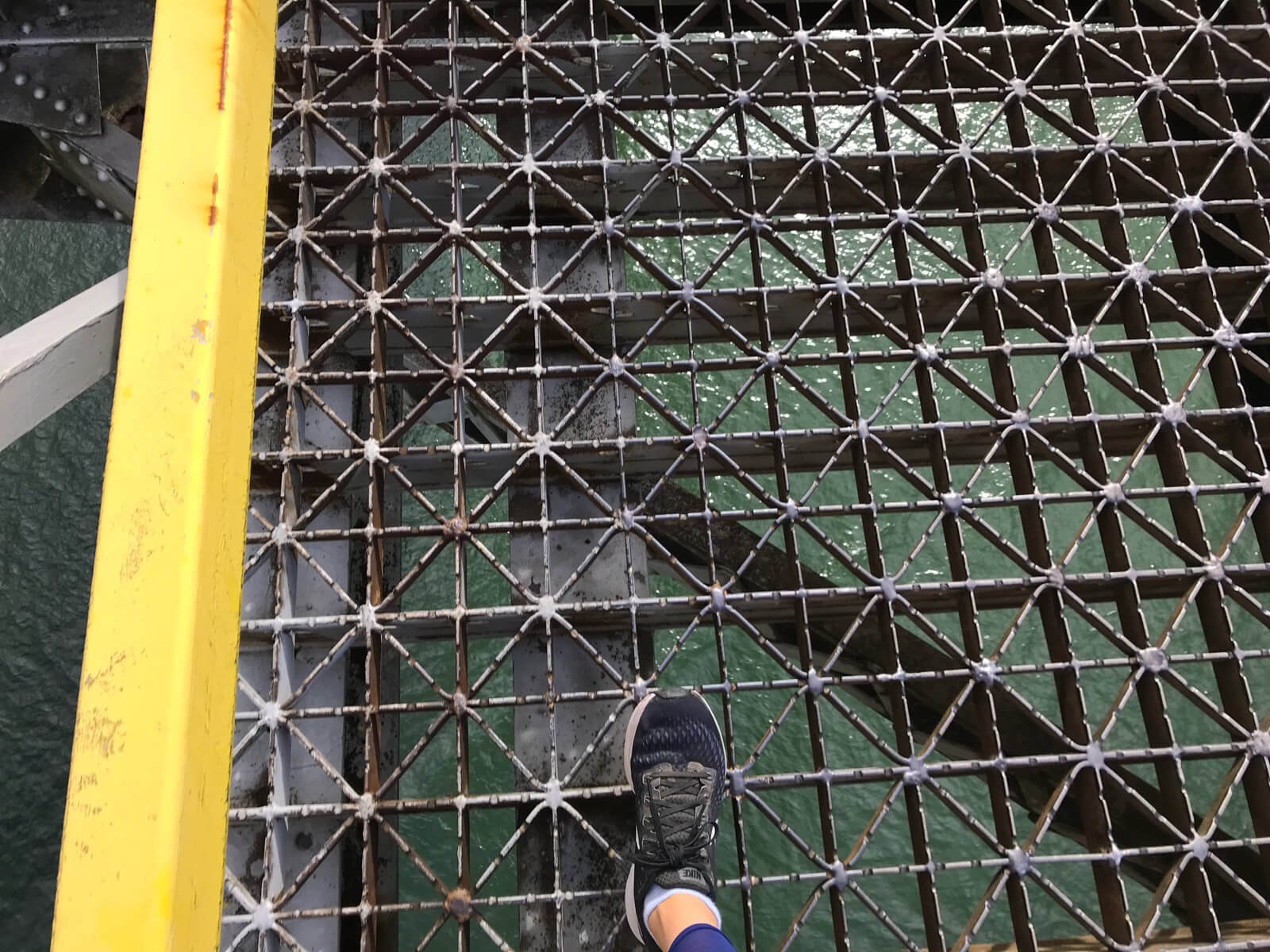 A birds-eye view of the walking surface of a bridge with water below. Someone's foot, wearing running shoes, is in the frame. The holes between the bridge structure look quite large.