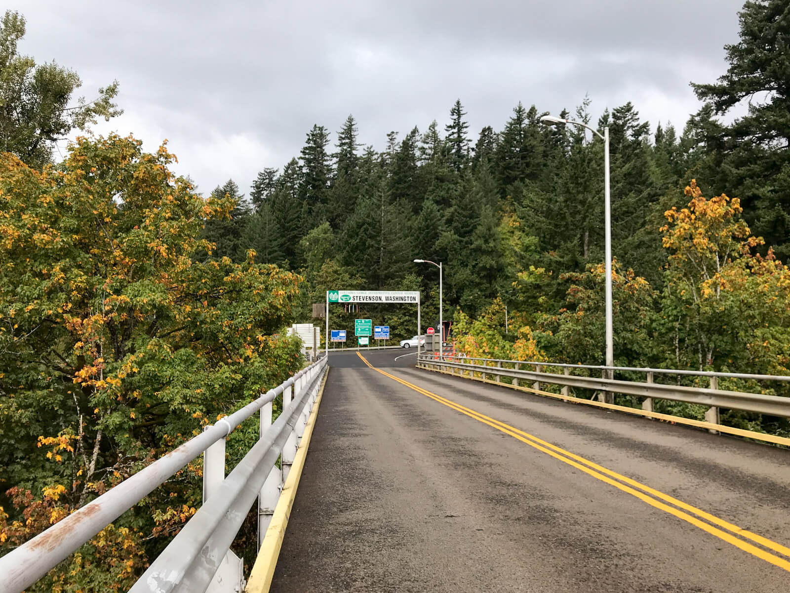 "A view on an elevated highway bridge, with a sign ahead reading ""Stevenson, Washington"", above the height of traffic. In the background are many green trees"