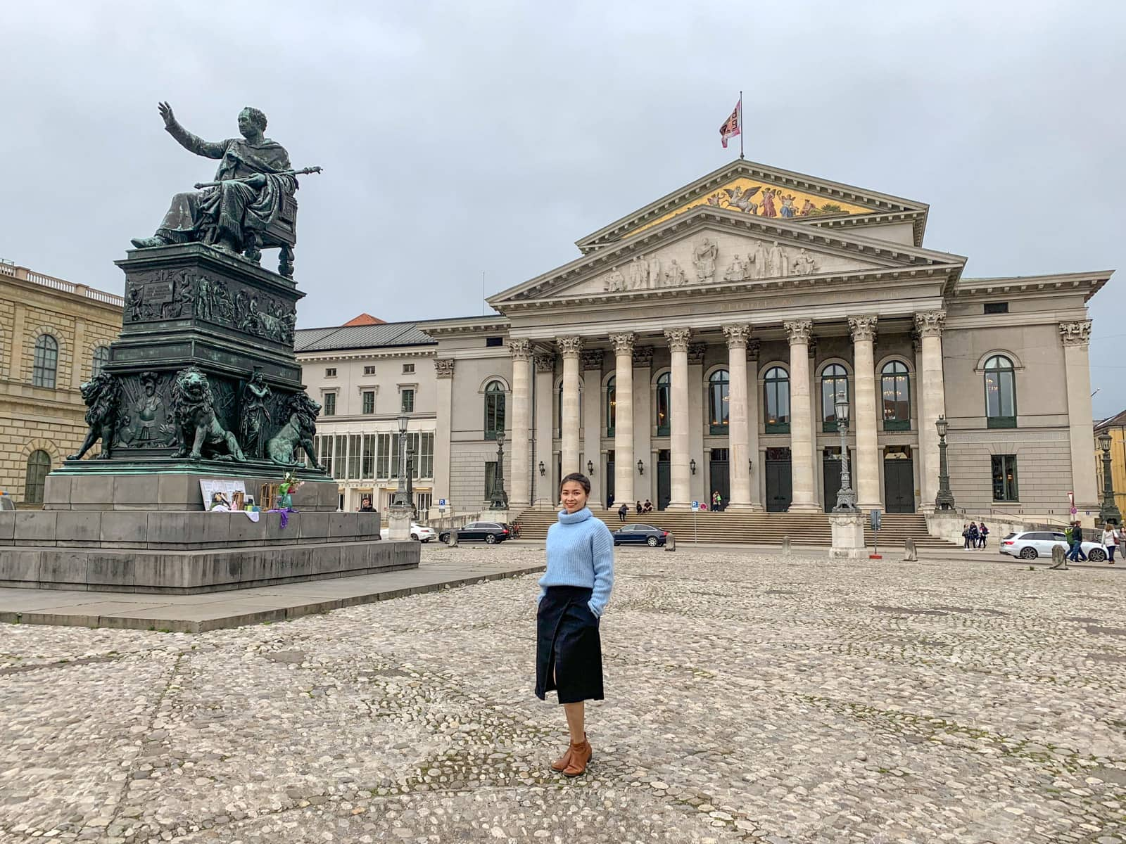 A woman in a blue sweater and black skirt in the foreground, she's standing in front of an old building in Munich