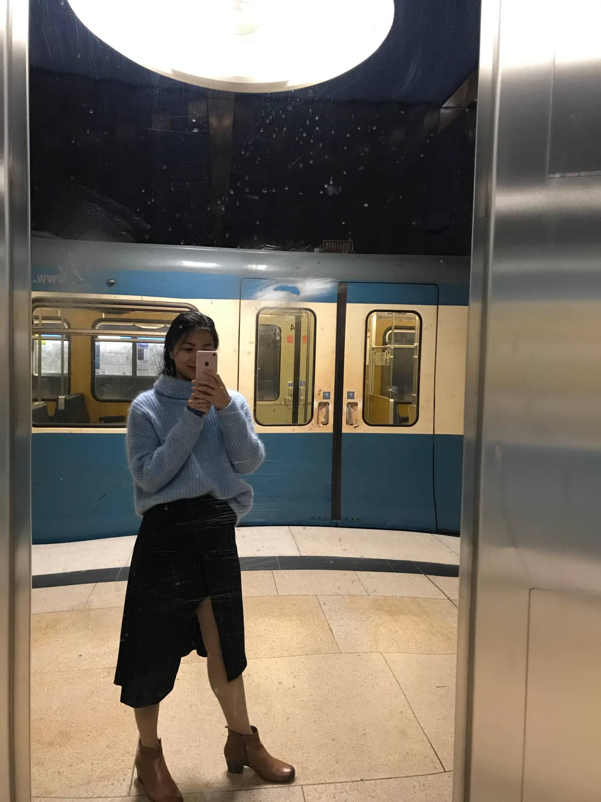 A woman in a blue sweater and a long black skirt, taking a selfie in a mirror at a train station. In the background is a blue train