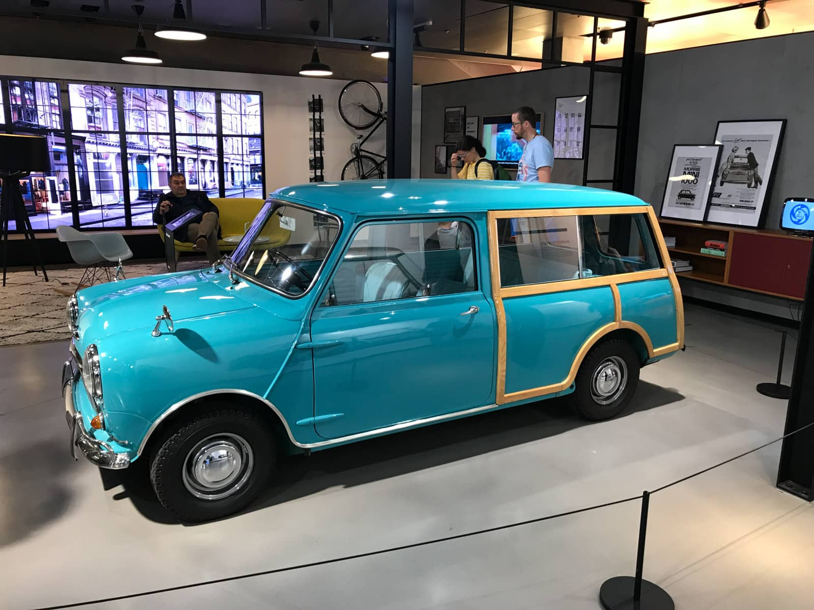 A small light cobalt blue coloured car being showcased indoors