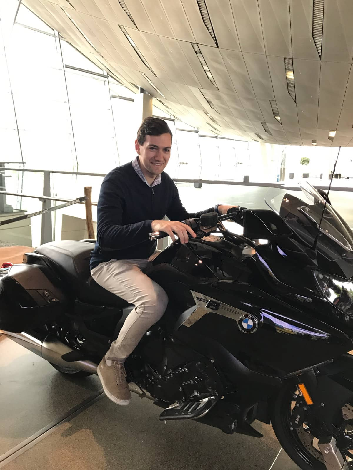 A man in a dark sweater and beige pants sitting on a motorbike in a museum