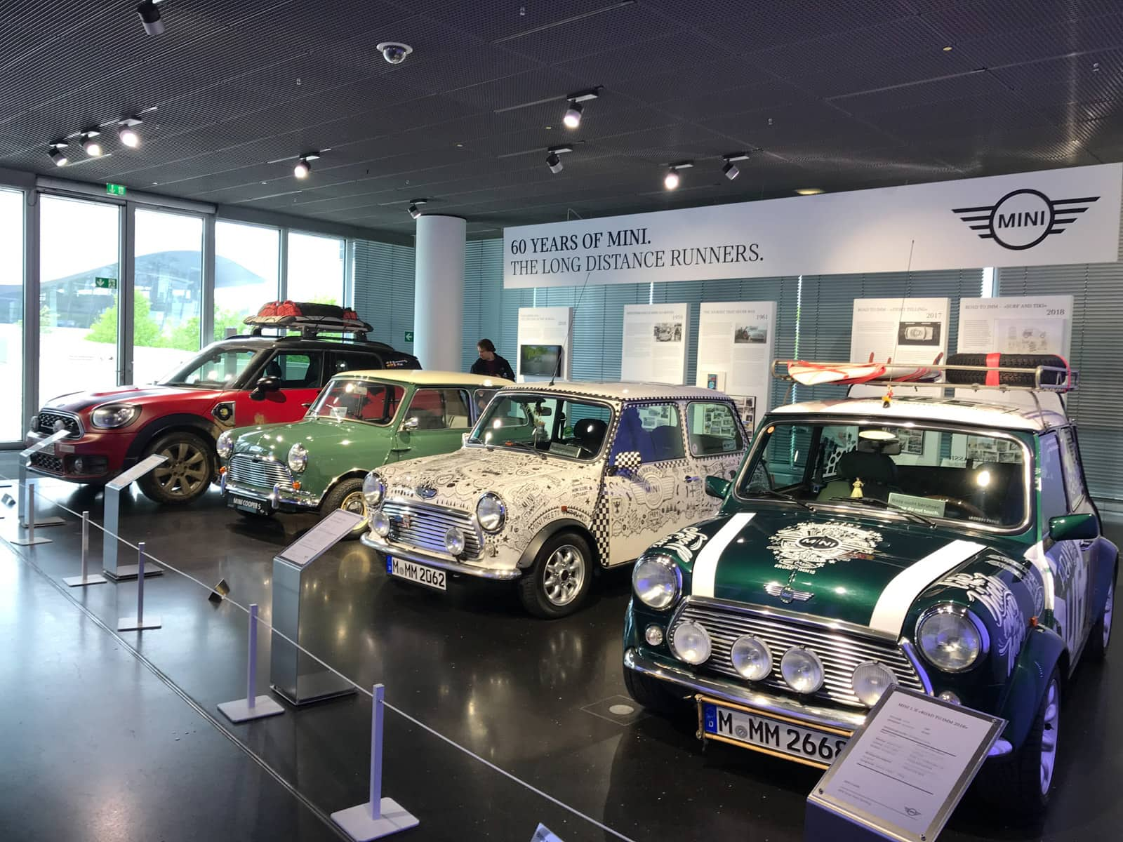 "Four Mini Cooper cars in a museum, in a row, in different colours. A banner behind them reads ""60 years of Mini. The long distance runners""."