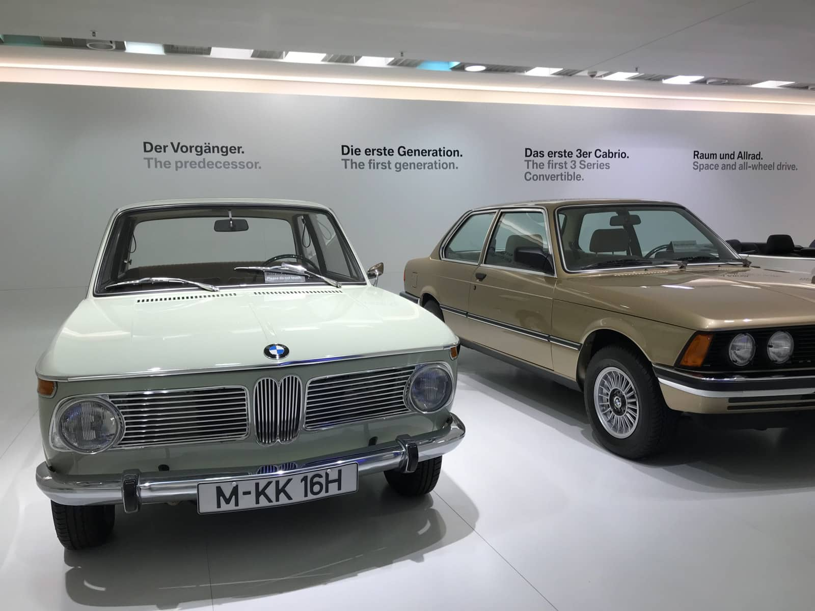 "Two BMW vehicles in a museum, labelled ""The predecessor"" and ""The first generation""."