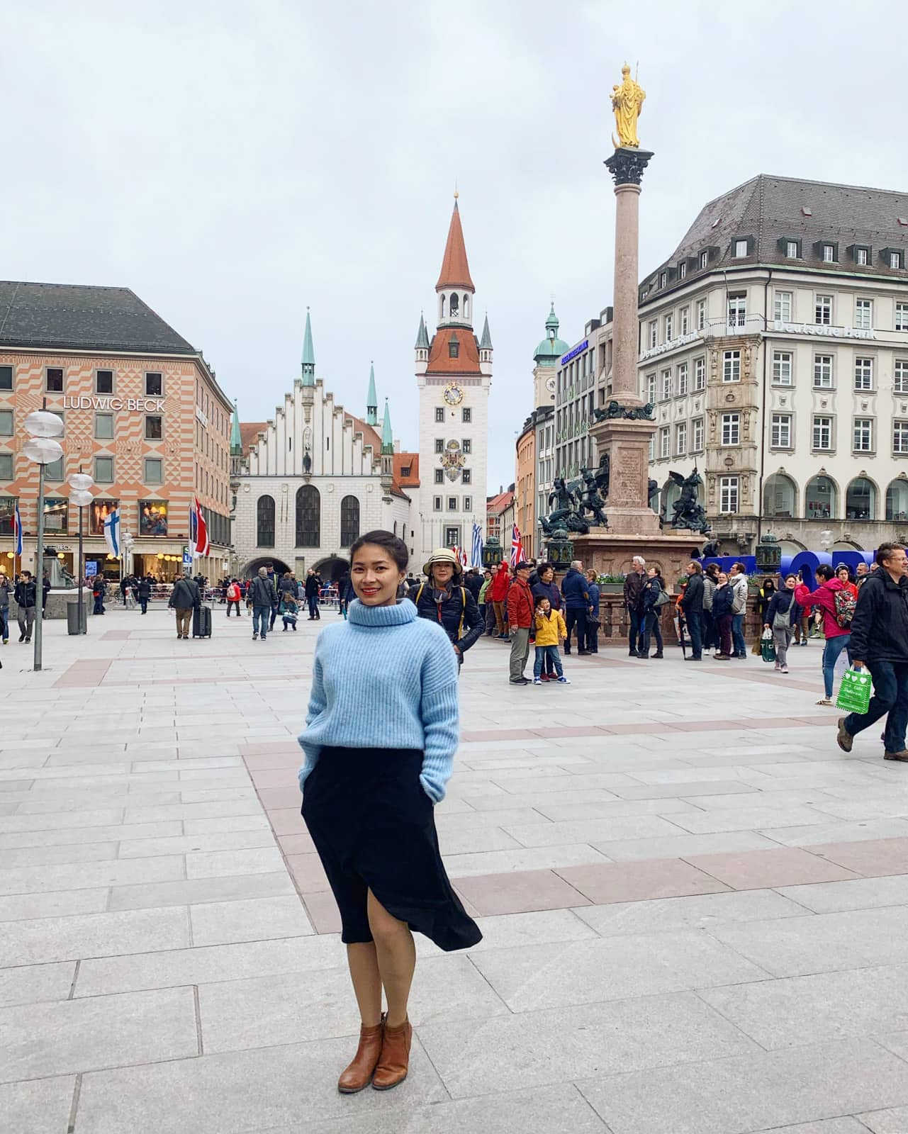 A woman in a blue sweater and black skirt in the foreground, she's standing in a town square in Munich where there are many people in the background as well as old but pretty buildings