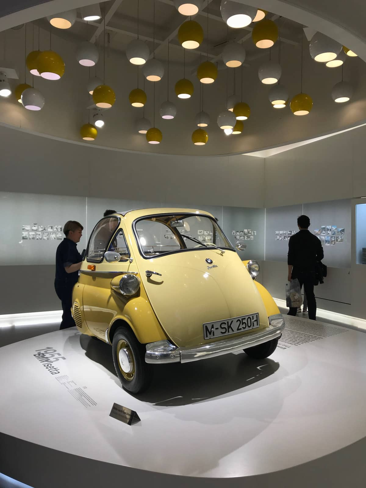 A small yellow car on display inside a museum