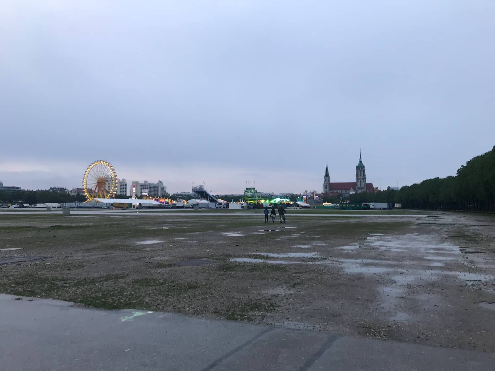 An open park area in the evening. The grass is wet from the rain. In the distance is a temporary festival ground set up with a ferris wheel and tents