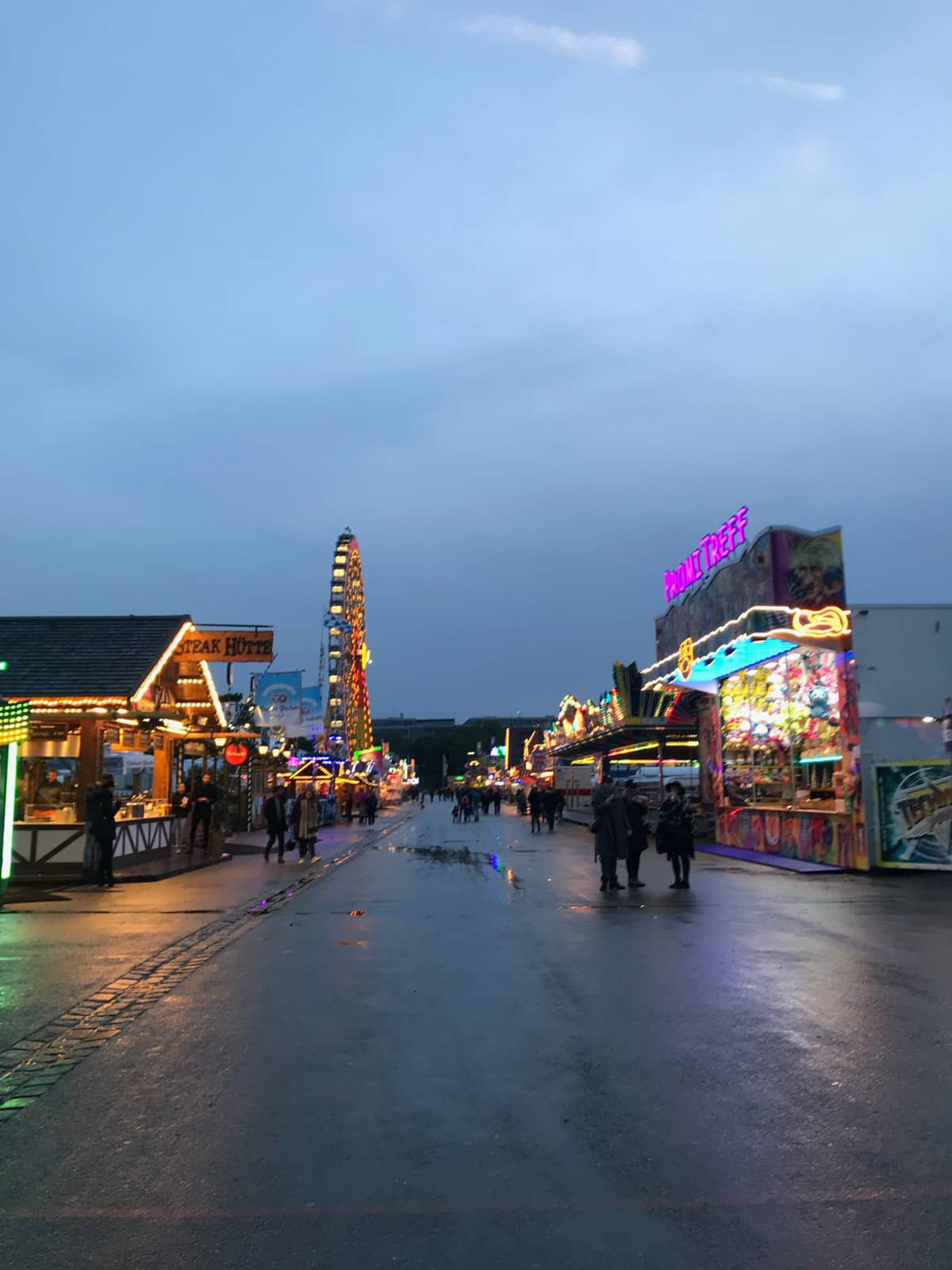 A temporary fairground area at night. The rides have their lights on.