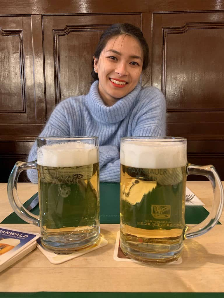 A woman wearing a blue sweater at a table with two big glasses of beer mixed with soda