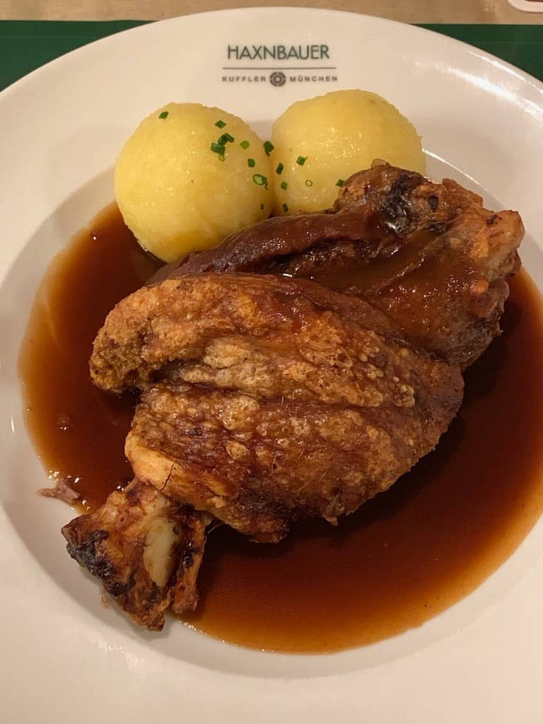 A plate with a serving of pork knuckle and sauce, with two round potato dumplings