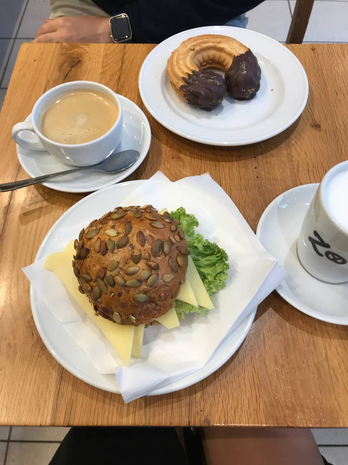 A small brown table with servings of coffee and two plates – one with a seed bun filled with cheese and lettuce, and the other with a chocolate dipped cookie