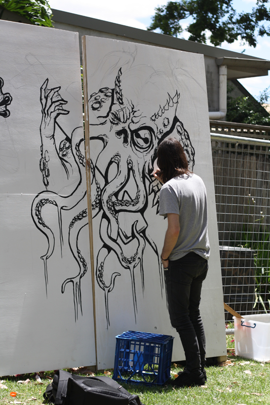 A young man painting artwork on a giant canvas