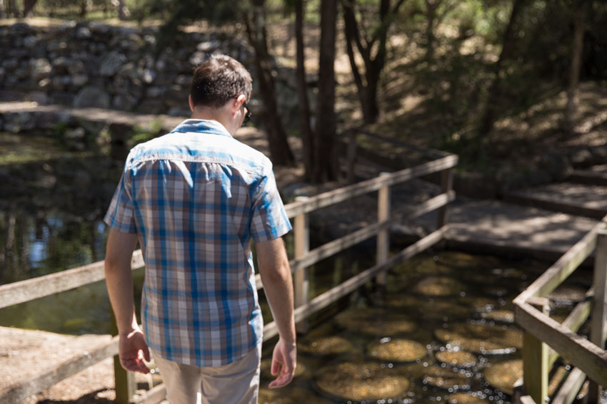 Me facing away from the camera about to cross a bridge of stepping stones