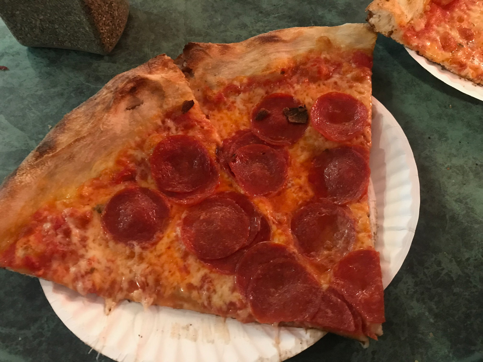 A few slices of pepperoni pizza on a white paper plate