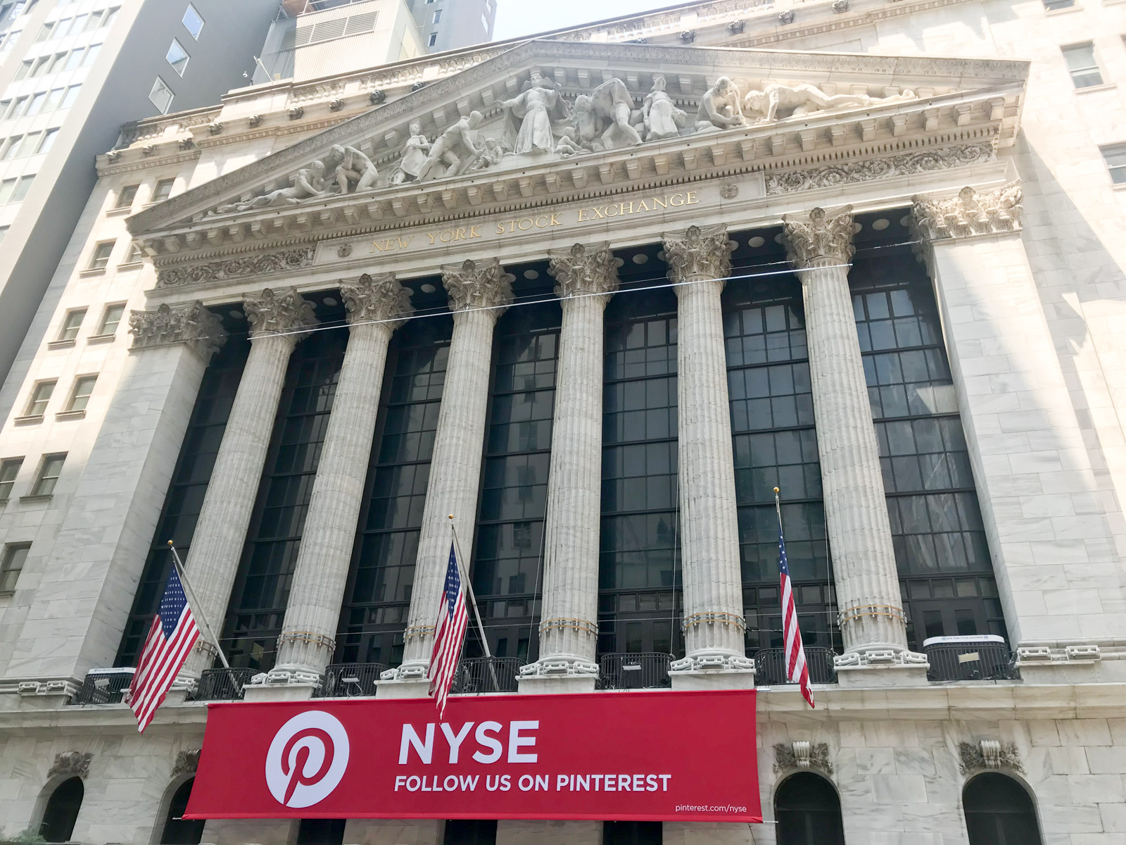 "A traditional stone building with lettering ""New York Stock Exchange"". Its front resembles pillars and tall windows"