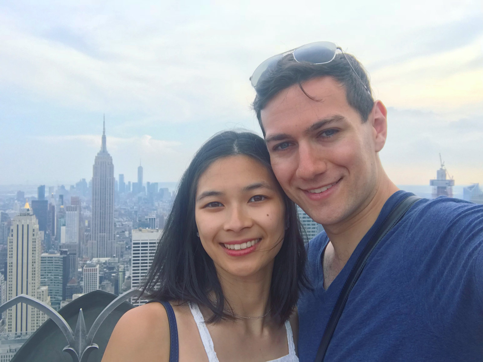 A selfie of a man and woman, smiling. The buildings of New York City are in the background.