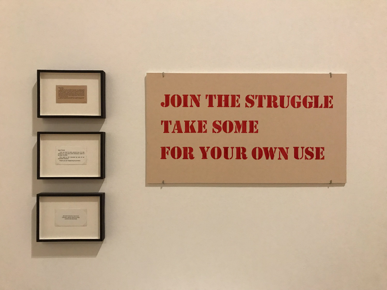 "Three small cards in a vertical line, framed in glass with black border. To the right is a beige sign in red uppercase text, reading ""Join the struggle. Take some for your own use�."