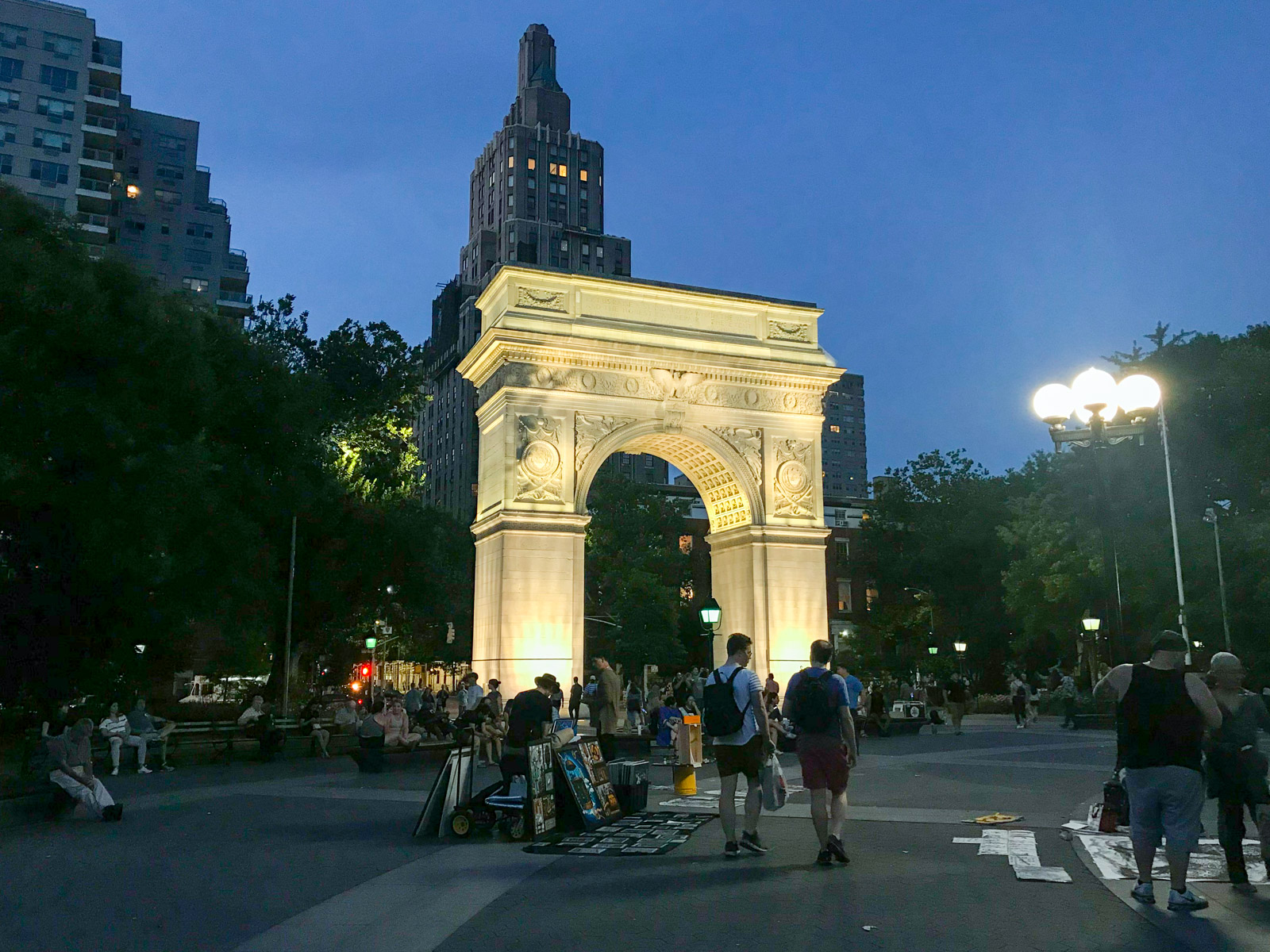 Washington Square Arch, a tall arch structure, lit up in the evening. In the foreground, people are sharing their artwork with it laid out on the ground