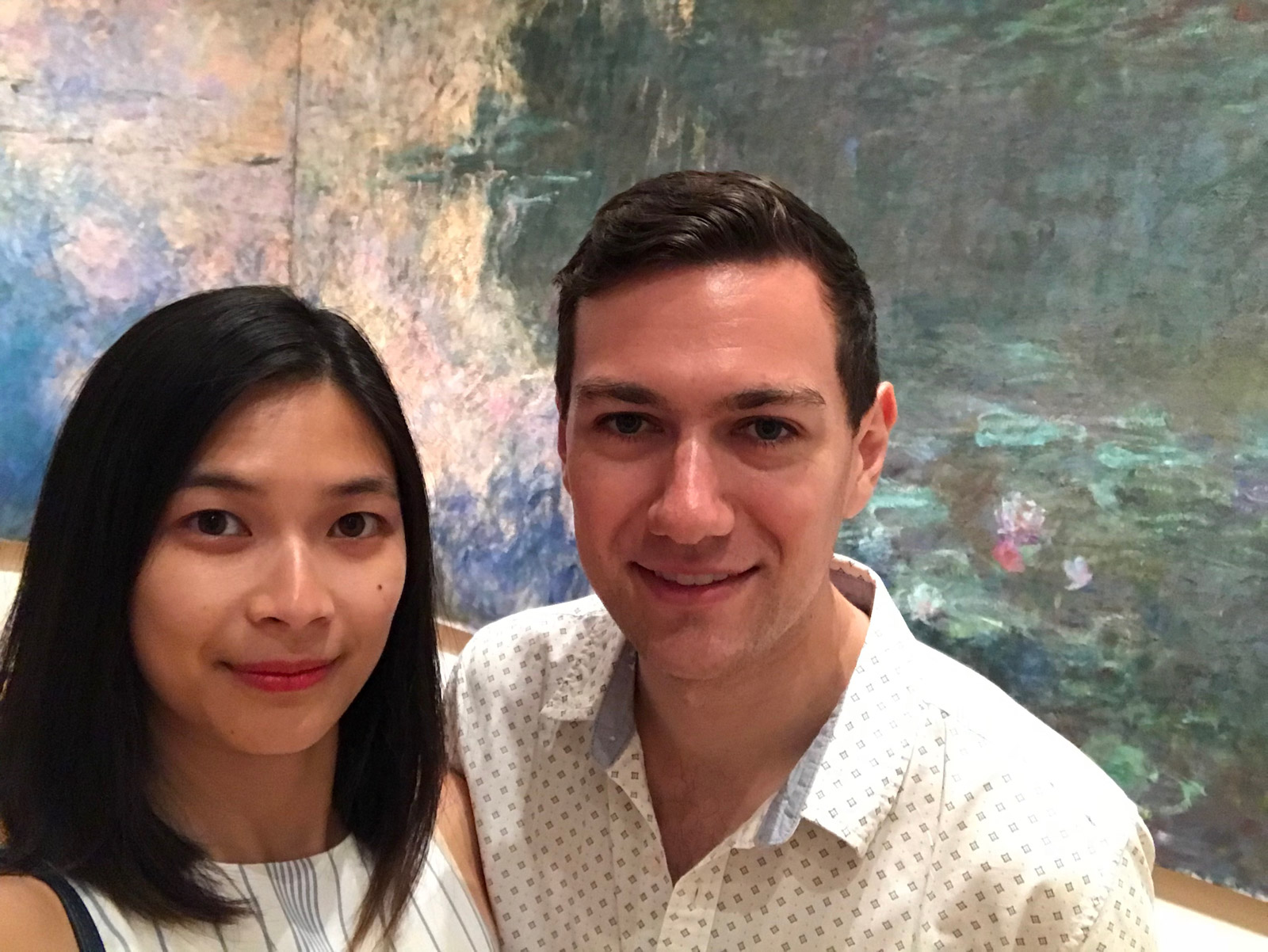 A man and woman, smiling, with a mural painting of water lilies behind them