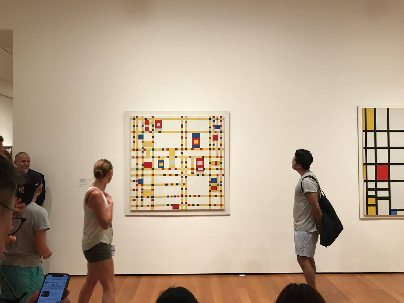 The inside of an art gallery with a geometric-style artwork of a Mondrian grid on the wall. Some people can be seen looking at it from the sides