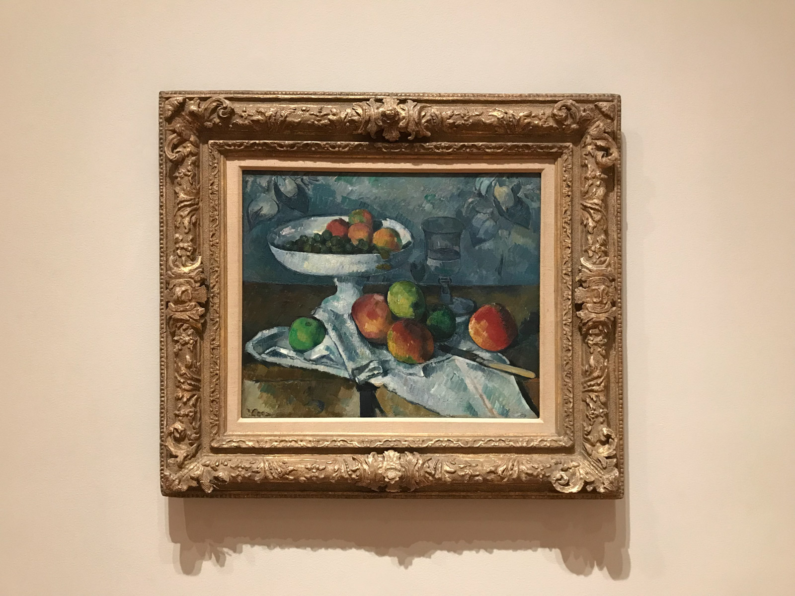 A framed painting of a bowl of apples, with some apples on the surface underneath