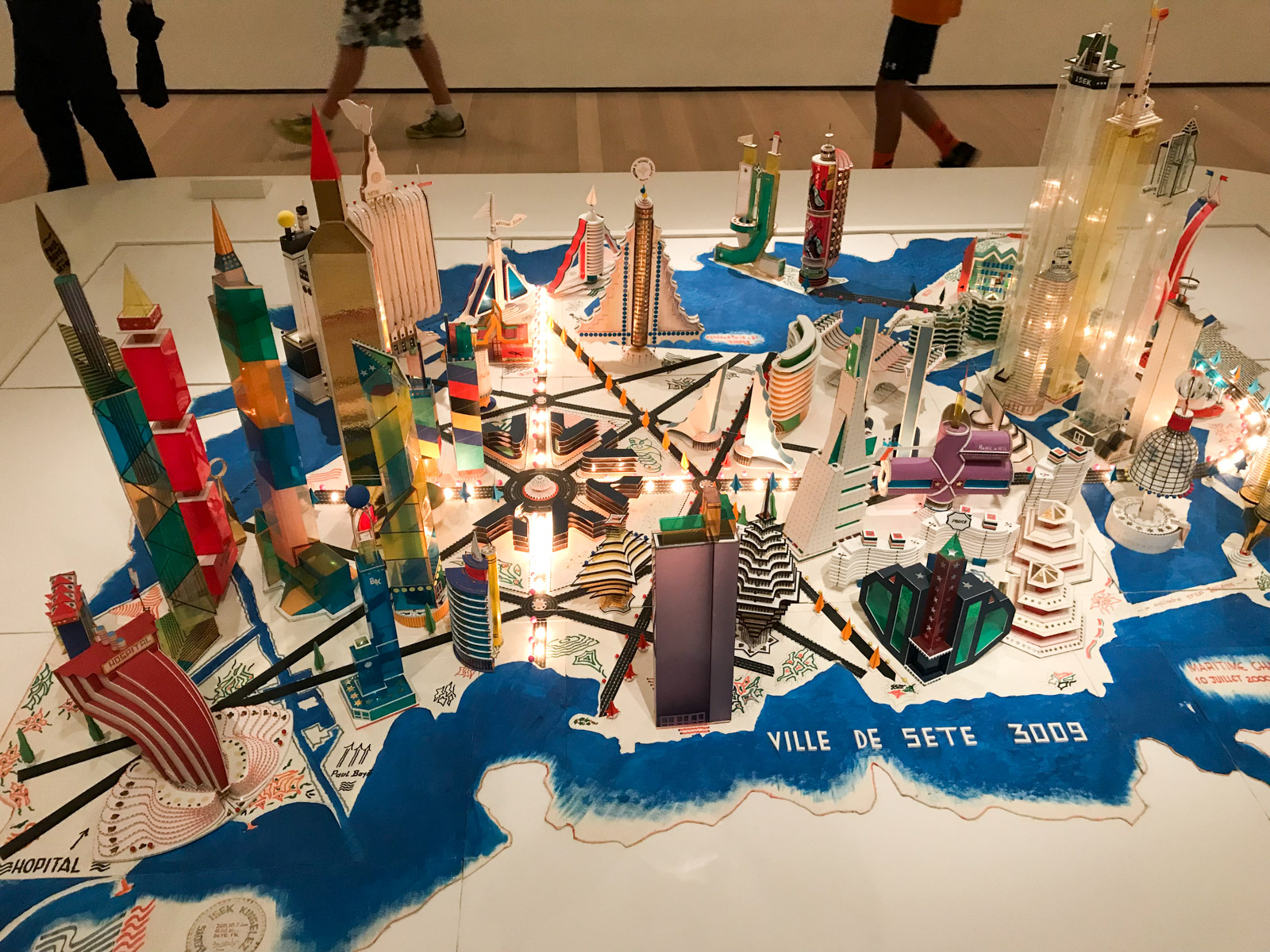 A high angle view of a sculpture made out of mostly coloured cardboard, assembled together like a city on an island