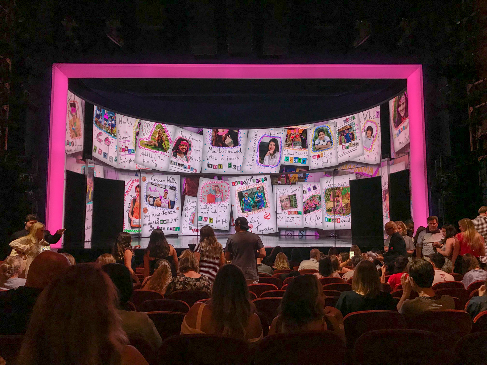 The inside of a theatre with audience members both sitting and making their way to their seats. The stage is ready with a digital backdrop resembling a scrapbook of photos and comments