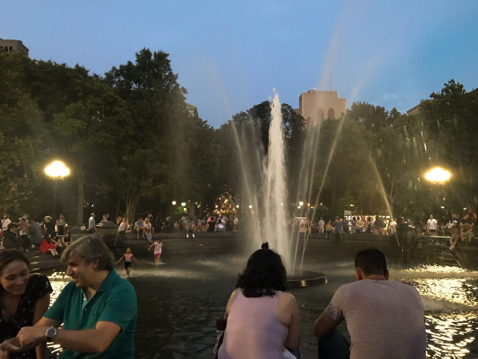 A nighttime view of many people sitting around a fountain. The fountain is active and jetting water.