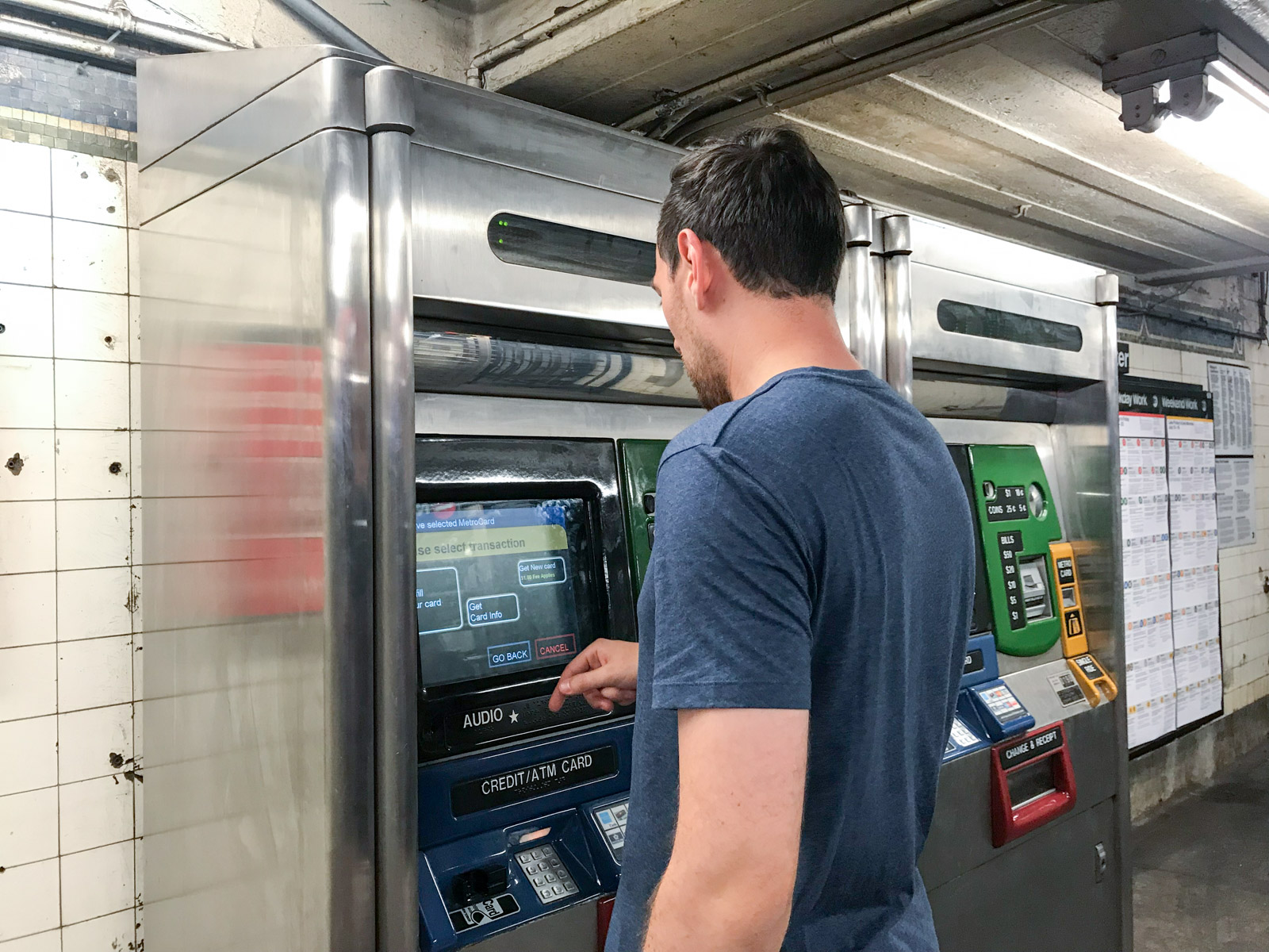 A man using a ticket machine to purchase subway tickets