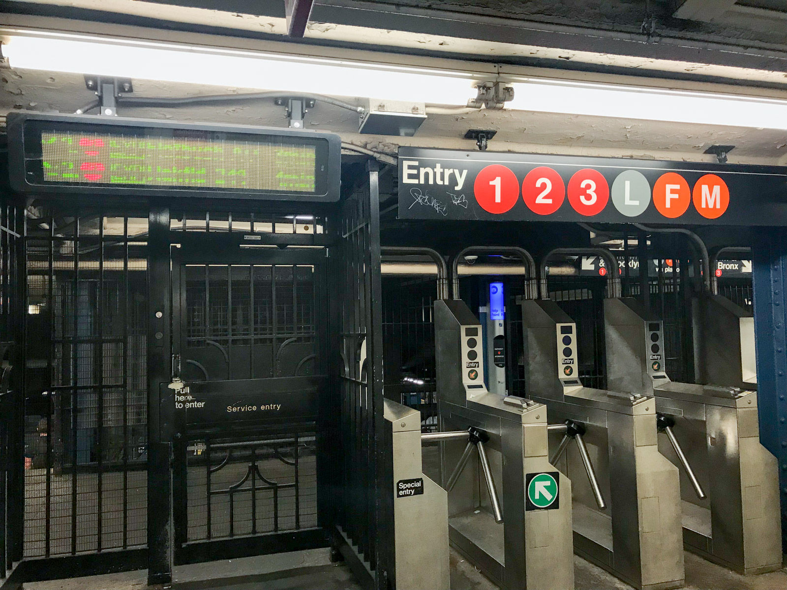 A row of turnstiles with subway lines printed on a sign above them. To the left is a black service entry/exit gate that resembles a door
