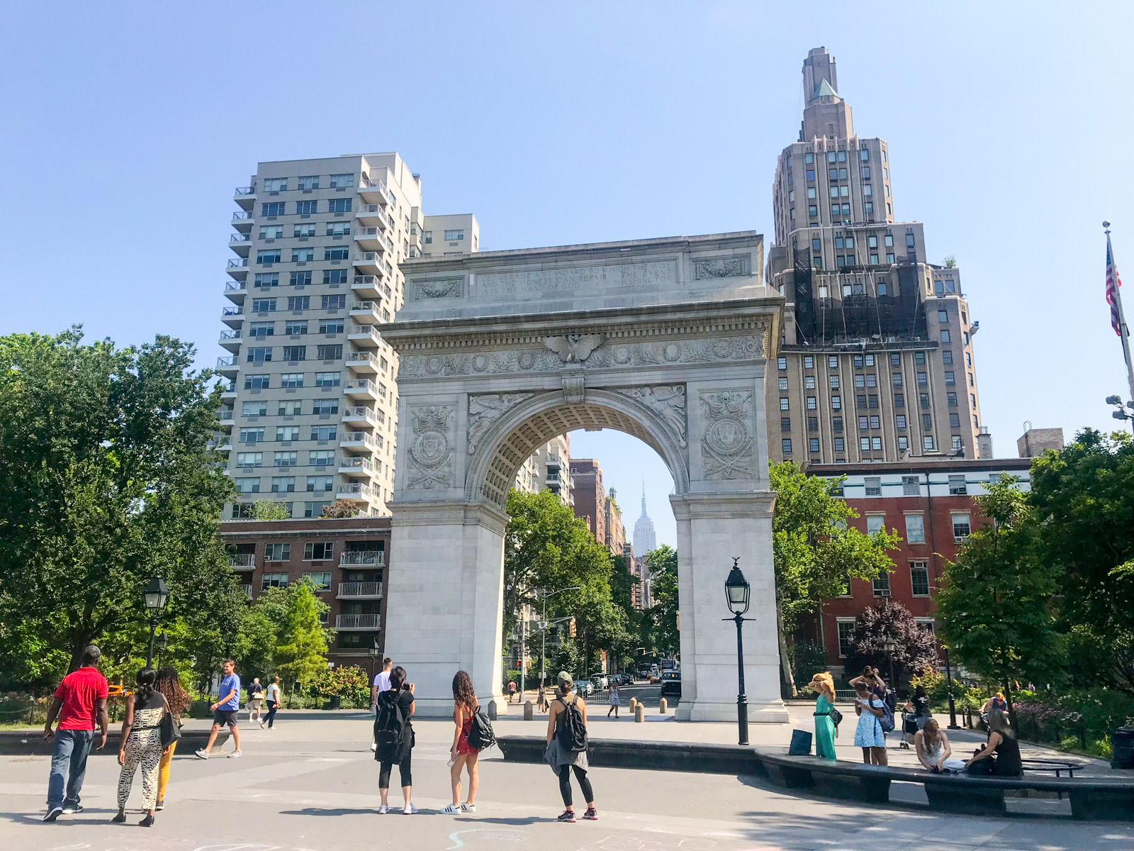 The Washington Square Park arch during the daytime. In the distance, the tall Empire State building can be seen through the arch.