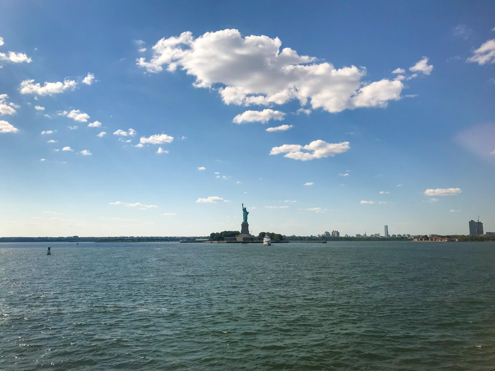 A view from a ferry of the Statue of Liberty, with a lot of the ocean visible around it. The sky is blue and has few clouds