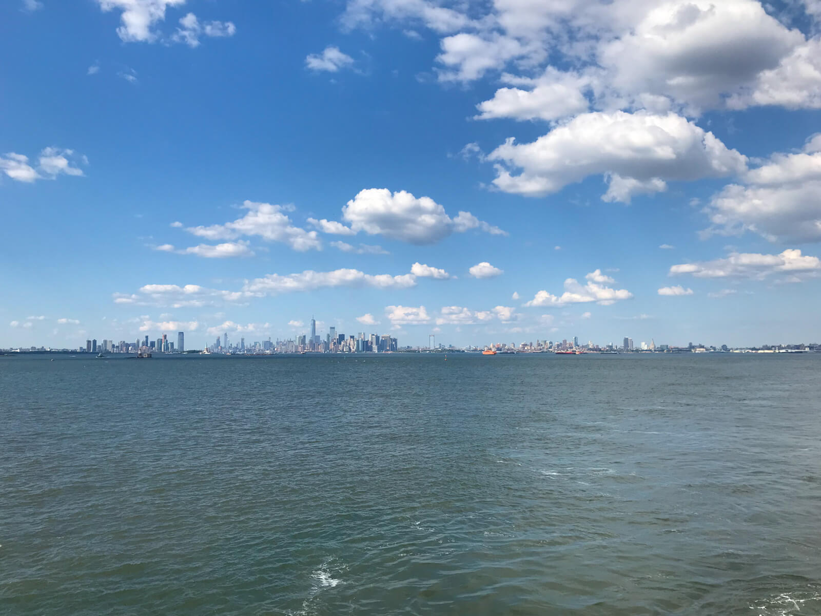 A city skyline with the ocean taking up the bottom half of the frame and blue sky with many clouds taking up the top half of the frame
